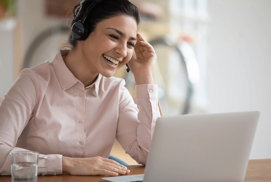 Smiling young woman wearing headset at her laptop