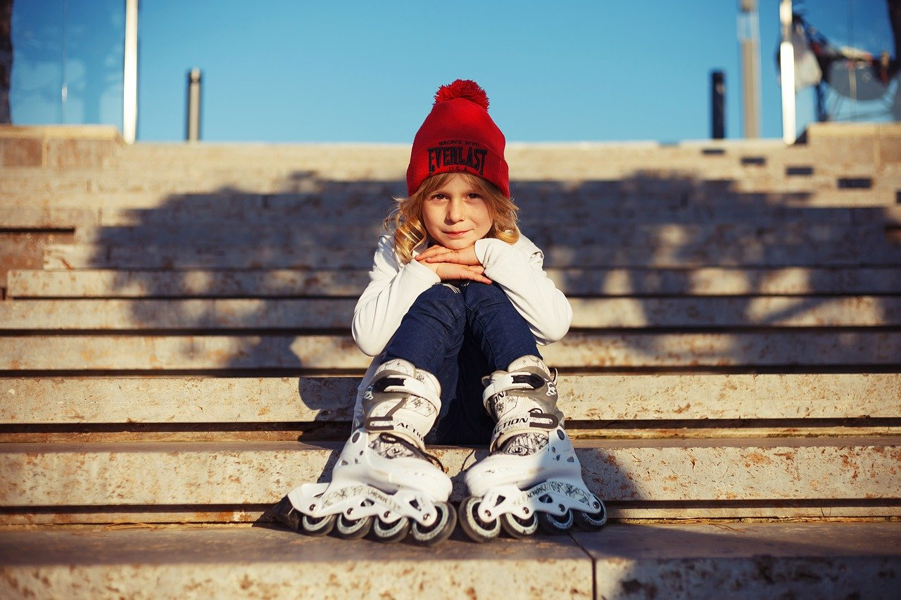 A little girl dressed in warm clothes and woolly hat and wearing roller blade boots on. She is sitting on stone steps.