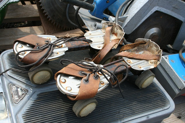 A very old pair of metal roller skates with leather ankle strap.